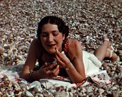 A colour still image showing a woman lying on a shingle beach putting on lipstick