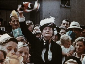 Woman in a hat waving a Union flag during a VE Day gathering