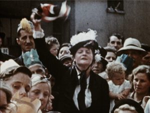 A colour still image showing a woman in a hat waving a Union flag during a VE Day gathering