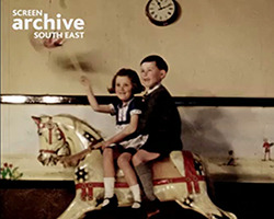 Two children sat on a rocking horse waving a union flag
