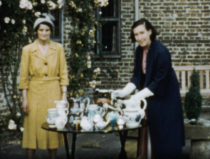 A colour image showing a portrait shot of two women from a W.I. group, stood next to a table laden with several jugs and crockery as a display