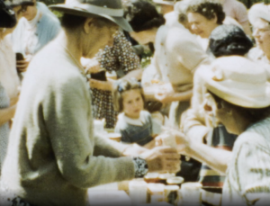 A close up image of a woman serving cups of tea at a refreshments stall during a large W.I gathering, in a garden.
