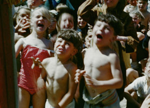 A colour still image showing a group of young children dressed in swimwear, watching a Punch and Judy puppet performance on Littlehampton beach.