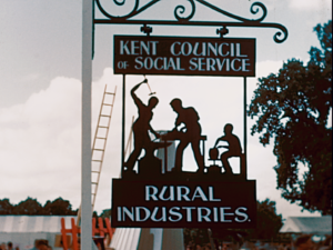 A colour image of the wrought iron Kent Council of Social Services Rural Industries sign, at the Kent Agricultural Show stand, 1951