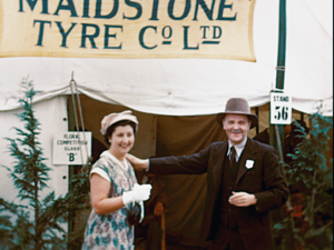 Image of a man and a woman stood together in front of the Maidstone Tyre company Ltd stand at the Kent Agricultural Show, 1951
