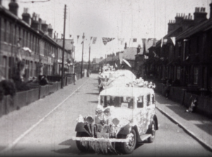 A black and white still image showing the local festivities of a car adorned with bunting in a parade honouring the 1935 Silver Jubilee of King George V and Queen Mary in Crawley