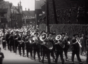 A black and white image showing a brass marching band during a parade in Crawley