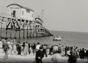 A black and white image of a lifeboat being launched at Selsey, watched by a large group of spectators in the foreground of the image.