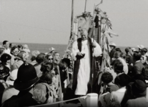 A black and white image showing a priest addressing a crowd during the blessing of a lifeboat launch, Selsey in 1938