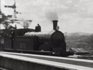 A black and white image of the boiler section of a train locomotive puffing steam at a station platform