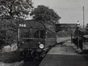 A black and white image of pair of railway carriages at a platform