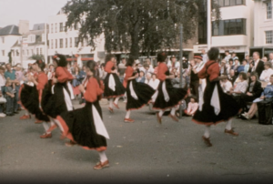 A colour image showing a group of folk dancers performing in a Horsham street.