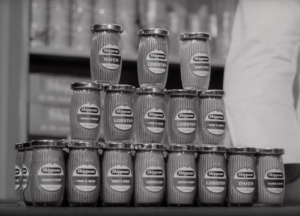 A black and white image of a three tier stack of Shippam's paste jars on a counter in a shop on display