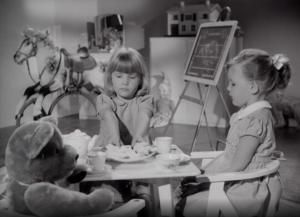 A trio of children sat around a low table having afternoon tea with Shippams paste filled sandwiches