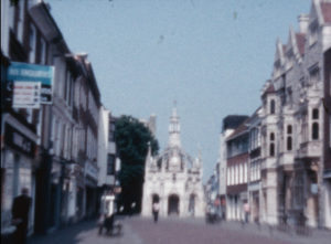 A colour still image showing A wide view of the Chichester Cross monument flanked by buildings on East Street, Chichester