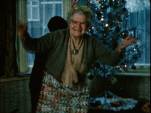 An image of an elderly lady dancing in front of her Christmas tree in the living room
