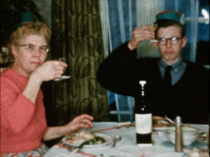 A man and a woman sat at a dining table holing up wine glasses to the camera in a toast, to health and wellbeing at Christmas