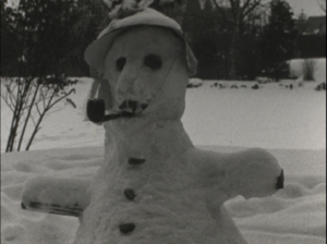 A black and white image of a snowman in a garden, smoking a pipe.