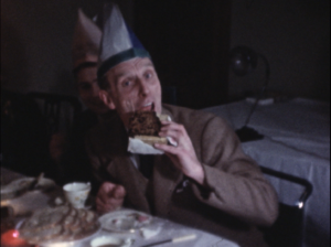 An older man eating a giant slice of Christmas cake whilst sat at a dining table, dressed in a Christmas party hat