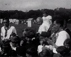 A black and white still image taken from TID 10106, showing a portrait style gathering group of workers, their children, volunteers and Reverend Miles Sargent stood together on Crowhurst Farm. The Reverend is supporting a young child that is sat on his shoulder.