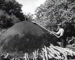A still from [Kent Hop Farming Part 2 - Making Charcoal] (1930s) showing a charcoal stack