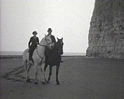 A still from [Town and Family Scenes at Broadstairs] (1929-1938) shwoing two people horseriding on the beach