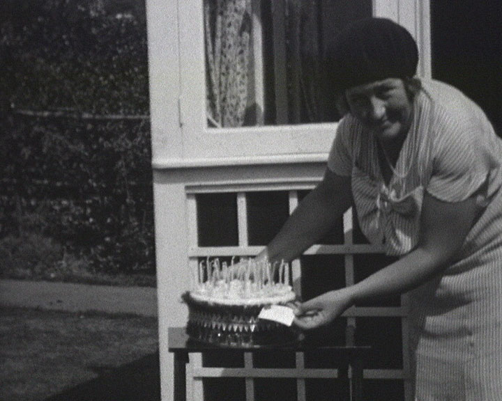 A still from [Broadstairs Items] (1927-1935) showing Enid Briggs with a cake