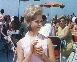 A still from 'A Date with the Sun' (1965) showing a woman at a cafe
