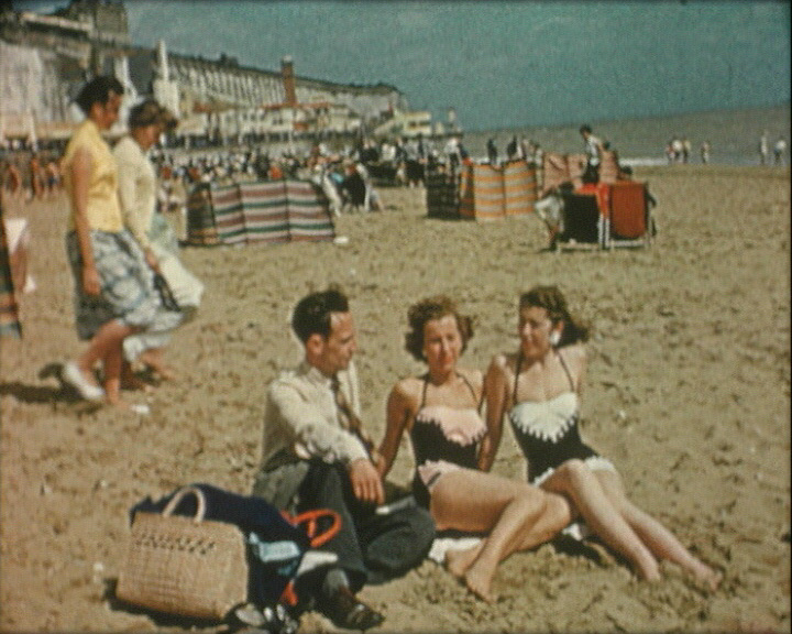 A still from 'At the Sign of the Ram and Gate' (1957) showing people on the beach