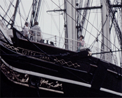 A colour still image taken from TID 10710, showing a close up of the bow of the Cutty Sark clipper with her name plate on her side and the family on board, as seen from land next to the ship.