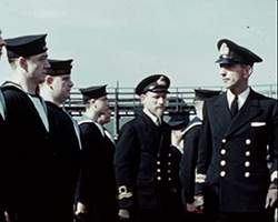 A colour still image taken from TID 10792, showing officers and Seamen of the Royal Navy on parade at a dockyard. The group are being inspected by their commanding officers and captain from the Flower Class Corvette, HMS Dianthus.