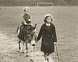 A black and white still image taken from TID 10809, showing the two year old boy taking a donkey ride through a football field. The toddler is sat on the back of a donkey in a long woollen coat, being led by a young girl also dressed in a long woollen coat. The girl is carrying a short bamboo cane and is looking shyly at the camera.