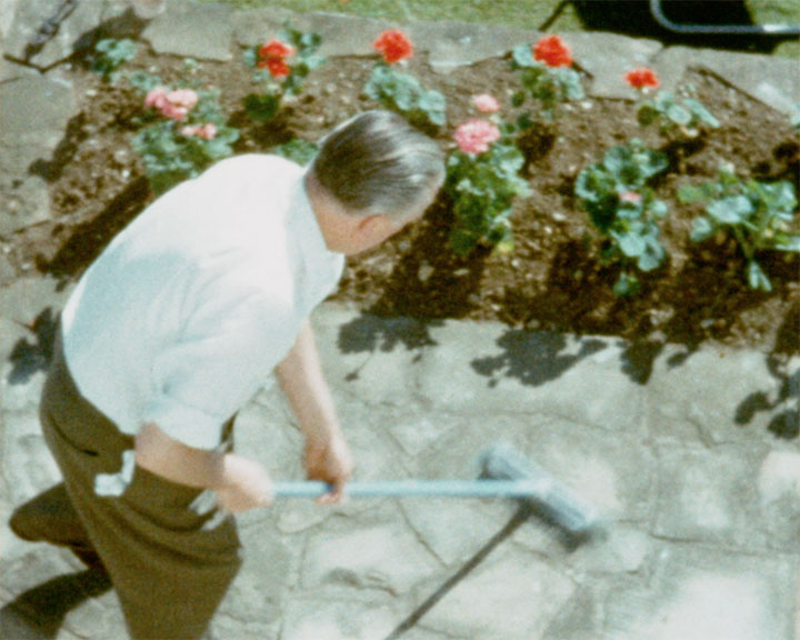 A colour still image taken from TID 10859 - Shoreham Harbour; Opening George Street (1962) showing an older man sweeping the steps and path of his garden terrace.