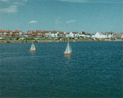 A colour still image taken from TID 10859 - Shoreham Harbour; Opening George Street (1962) showing two model yachts that are being sailed on still waters at Shoreham Harbour.