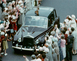 A colour still image taken from TID 10859 - Shoreham Harbour; Opening George Street (1962) showing Queen Elizabeth and Prince Philip in a rolls Royce traveling down the newly restored and re-opened George Street. Crowds wave as the Royal couple are driven away in their new car.