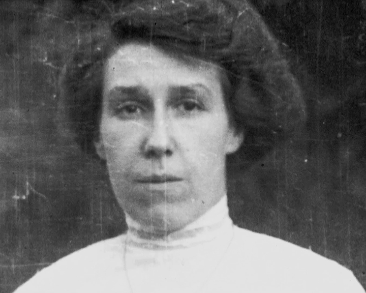 A black and white still image taken from TID 10960, showing a portrait style image of Bessie Lauste. Bessie has a neutral expression on her face, as she poses for the camera dressed in a long sleeved high collar white shirt.