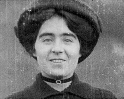 A black and white still image taken from TID 10960, showing a portrait style image of Marguerite, aged in her early twenties. Marguerite is dressed in a hat and Edwardian cameo choker necklet, smiling as she poses for the camera.