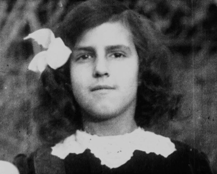 A black and white still image taken from TID 10960, showing a portrait style image of Doris Lauste aged about 10 years old. Doris is dressed in a dress with a frilly collar and wearing a white ribbon on one side of her hair, smiling as she poses for the camera.