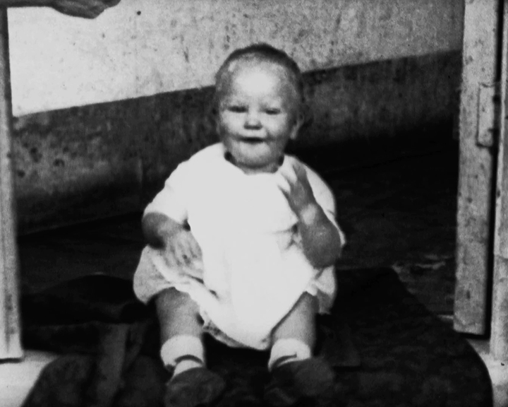 A black and white still image taken from TID 10960, showing a portrait style image of Alva Lauste, a toddler aged about two years old. Alva is dressed in a white tunic style outfit sat on a step in a doorway, smiling as he looks at the camera.