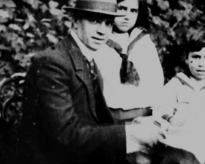 A black and white still image taken from TID 10960, showing a group portrait of Emile, Leslie and Doris sat together at a garden table posing for the camera. The children are dressed in sailor style outfits, with Emile in a day suit and hat holding a newspaper.