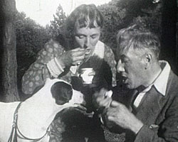 A still from 'Sunday Afternoon Interlude' (1937-1938) showing people feeding icecream to a dog