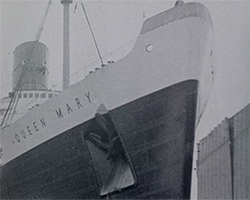 A black and white still image taken from TID 1137, showing a close up view of the bow of RMS Queen Mary. Her name is visible, painted on her side.