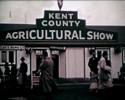 A colour still image taken from TID 11560, showing a wide view of the main entrance with signage above the gate to the exhibition ground. The sign reads Kent County Agricultural Show.
