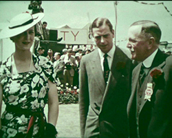 A colour still image taken from TID 11572, showing a close up shot of the interior of one of the main show marquees at the Kent Agricultural Show, Canterbury. HRH Prince George, Duke of Kent, HRH Marina, Dutchess of Kent; and Society President Mr W.K. Whigham stand together talking as other guests arrive for the show.