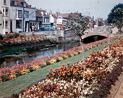 A colour still from the film Canterbury (1962) showing the great Stour River passing through Westgate Gardens in full bloom around paths of grassy lawn. A red and white bus is seen on Westgate Grovenext to a small road bridge over the river.}