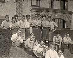 A wide black and white still image taken from TID 12261, showing a group of boys aged between 12-15 years old stood or sat on a flight of brick steps, outside of a large brick building. The boys are dressed in a uniform consisting of a short sleeved shirt and shorts.