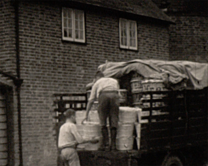 A black and white still image taken from TID 12262, showing two older teenage boys loading produce from Goudhurst Farm on to the back of an open commercial vehicle. One boy is stood on the tail end of the truck, whilst the other boy passes up produce from the ground.