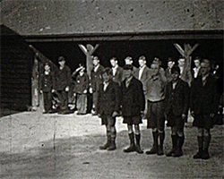 A wide black and white still image taken from TID 12264, showing a group of boys stood in two neat rows facing forward, on a parade style military inspection. The boys are dressed in their winter woollen farm uniform,  in the entrance to a shelter style farm barn building on the Goudhurst Farm home estate.