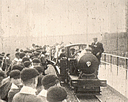 A wide black and white still image taken from TID 12266, showing a group of boys from the Feagan's home standing on a platform waiting for a narrow gauge Romney, Hythe and Dymchurch railway locomotive with carriages, to pull into the station platform.