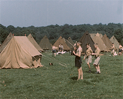 A colour still image taken from TID 12268, showing a group of large pale brown canvas tents erected in a field, with a group of Feagan's boys stood in the foreground talking to each other.